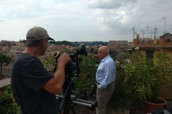 Marco d'Eramo on the roof terrace of his Rome apartment, with the Colosseum in the background. Filmed by cameraman Marc Nordbruch. © NOW Collective / Jörg Leine.