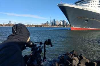 Die Queen Mary 2 am Hafen in Red Hook in Brooklyn. Im Hintergrund Manhattan. Gut verpackt: Kameramann Marc Nordbruch. © NOW Collective / Jörg Leine.
