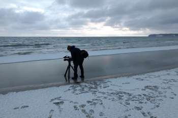 The first snow on the beach at Prora. Cameraman Marc Nordbruch at the water's edge. © NOW Collective / Jörg Leine