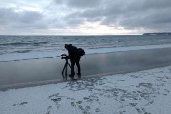 Der erste Schnee am Strand von Prora. Kamermann Marc Nordbruch am Wasser. © NOW Collective / Jörg Leine